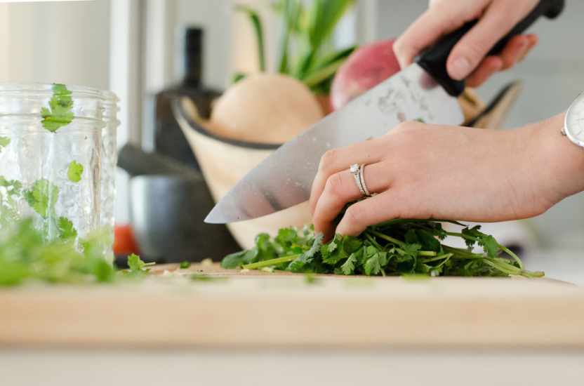 Person chopping herbs on cutting board